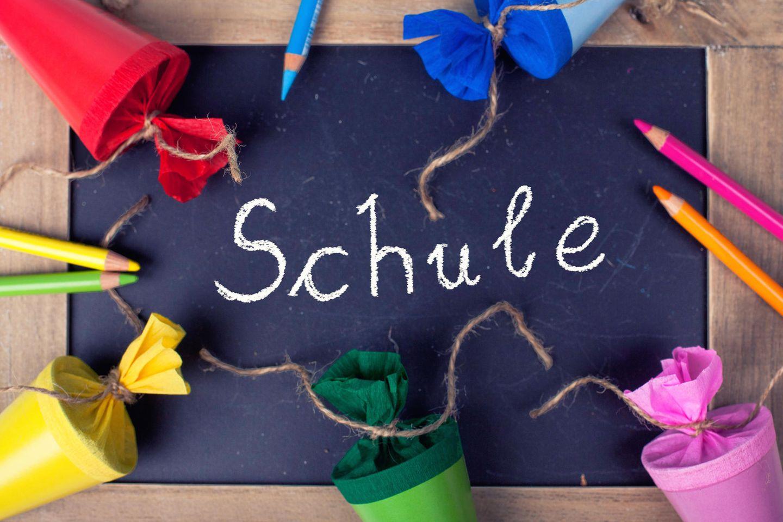"""Einschulung, bunte Schultüten, bunte Buntstifte, schwarze Tafel mit """"Schule"""" als Aufschrift"""