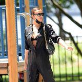 Boilersuits sind langweilig? Ganz im Gegenteil! Irina Shayk trägt ihren schwarzen weit aufgeknöpft, und der hervorblitzende BH macht diese Style-Kombi zu einem echten Hingucker.