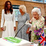 """11. Juni 2021  In Begleitung von Herzogin Camilla und Herzogin Catherinenimmt Queen Elizabeth an einer Veranstaltung der Kennenlern-Initiative """"The Big Lunch"""" unter der Federführung des """"Eden Project"""" im Rahmen des G7-Gipfels in Bodelva, Cornwall, teil.Dabei zeigtdie Königin ihren Nachfolgerinnen ziemlich schlagfertig, wie man als Royal standesgemäß einen Kuchen anschneidet.Denn statt zu einem normalen Messer zu greifen, borgt sich die Königin kurzerhand das große Zeremonienschwert des Lord Lieutenant of Cornwallund beeindruckt damit die anwesenden Gäste."""