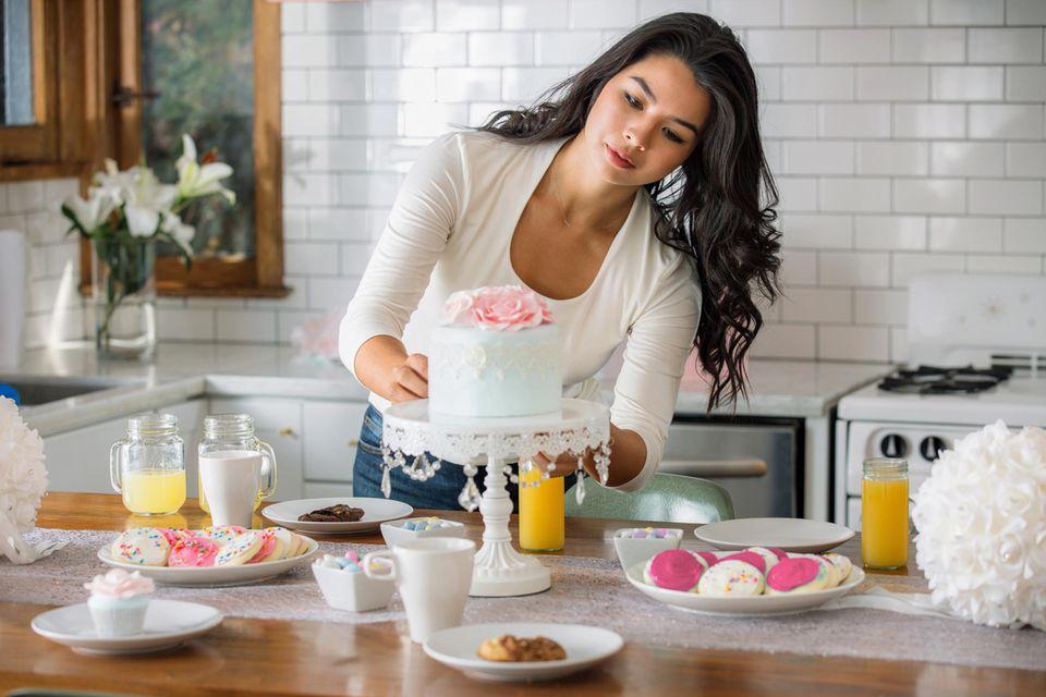 Hochzeitstorte selber machen: So gelingts zu Hause, eine Frau mit dunklen Haaren dekoriert einen Kuchen auf einer Tortenplatte
