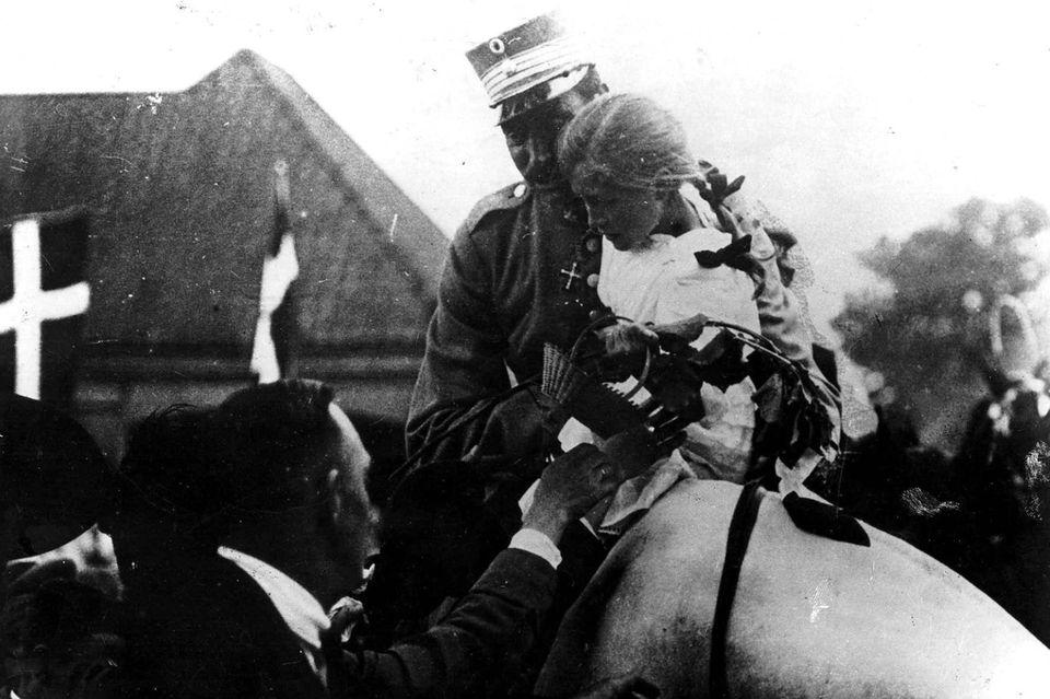 König Christian X durchreitet am10. Juli 1920 auf seinemPferd Malgré Tout der neunjährigen Johanne Herlak im Arm die alte Grenze bei Fredrikshöj südlich der Stadt Kolding.