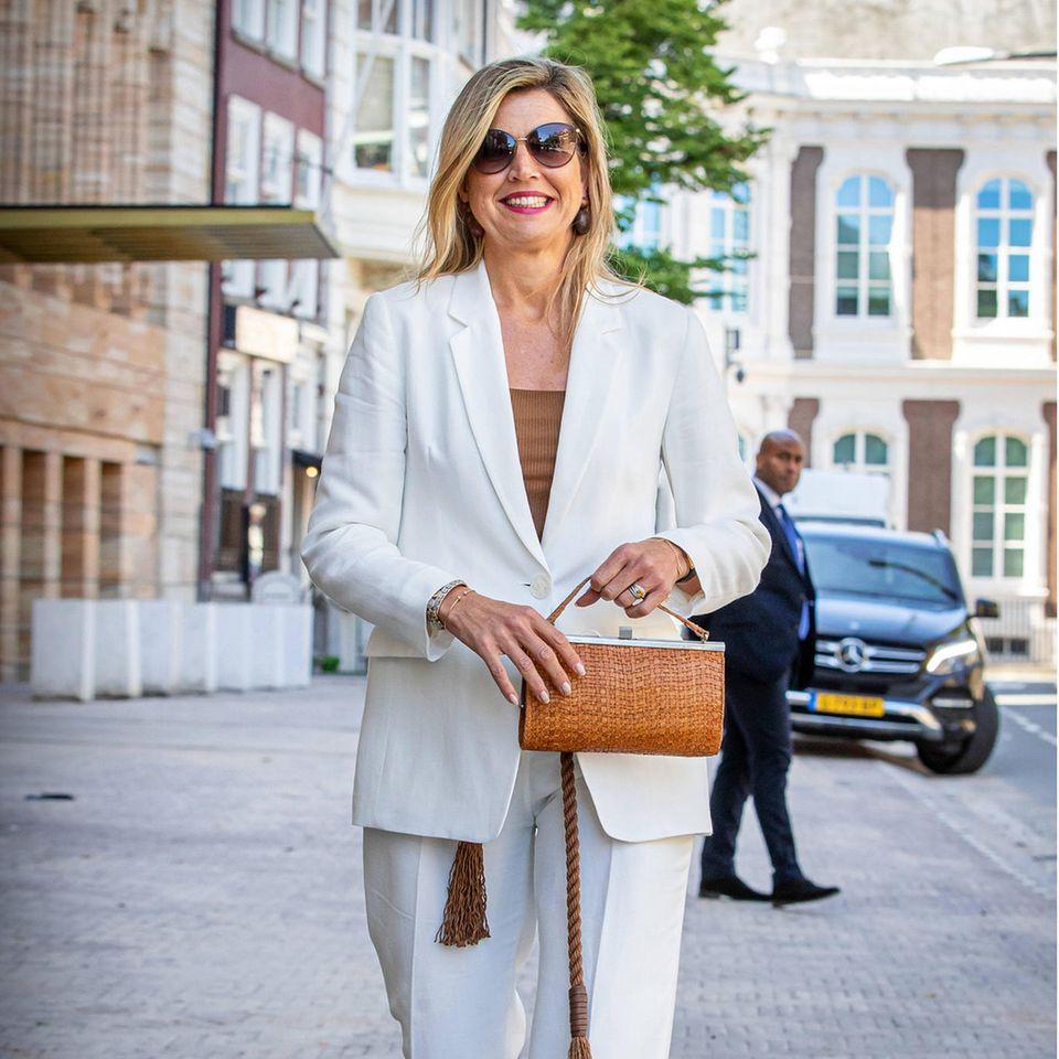 """Aufgepasst, hier kommt die Style-Queen! Königin Máxima strahlt bei einem virtuellen Symposium der Plattform """"Wijzer in Geldzaken"""" in Den Haag in ihrem weißen Sommer-Anzug mit hellbraunem Top und passenden Accessoires richtig gute Laune aus. Und die ist einfach ansteckend."""