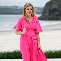 Pretty in Pink: Carrie Johnson leuchtet auch bei mäßigem südenglischen Wetter in ihrem knalligen Roksanda-Dress.Ein Schnäppchen ist der sommerliche Look mit gut 1600 Euro nicht, aber die First Lady trägt auch diesen Look lediglich als gemietetes Outfit von Wardrobe HQ. Das ist nicht nur nachhaltig, sondern auch vorbildlich!