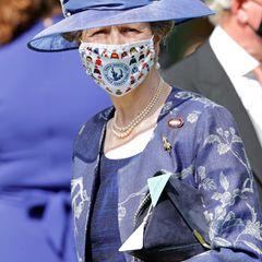 """Auch Charles Schwester, Prinzessin Anne , lässt sich den royalen Spaß nicht entgehen. Zu ihrem Outfit in Lila trägt sie eine Maske mit Jockey-Motiven des """"Injured Jockeys Fund"""". Sie ist Schirmherrin des Organisation, die die Rehabilitation verletzter Spielerunterstützt."""