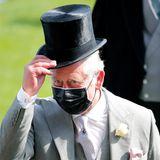 Prinz Charles zieht den schwarzen Zylinder vor den vielen gutgekleideten Gästen des Events. Dazu trägt er einen grauen Anzug mit rosa Anstecktuch.