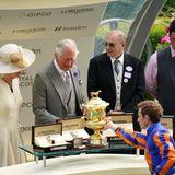 """Jockey Ryan Moore darf sich über eine Trophäe freuen, die ihm von Herzogin Camilla und Prinz Charles nach dem Sieg mit seinem Pferd """"Love"""" überreicht wird."""
