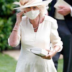 Herzogin Camilla lässt sich nicht lange bitten und besucht gemeinsam mit Ehemann Prinz Charlesauch am zweiten Tag das Pferderennen in Ascot. Dafür setzt sieauf ein zartgelbes Kleid von Fiona Clare Couture mit passendem Mund-Nasen-Schutz sowie einen farblich perfekt darauf abgestimmten Hut von Philip Treacy.