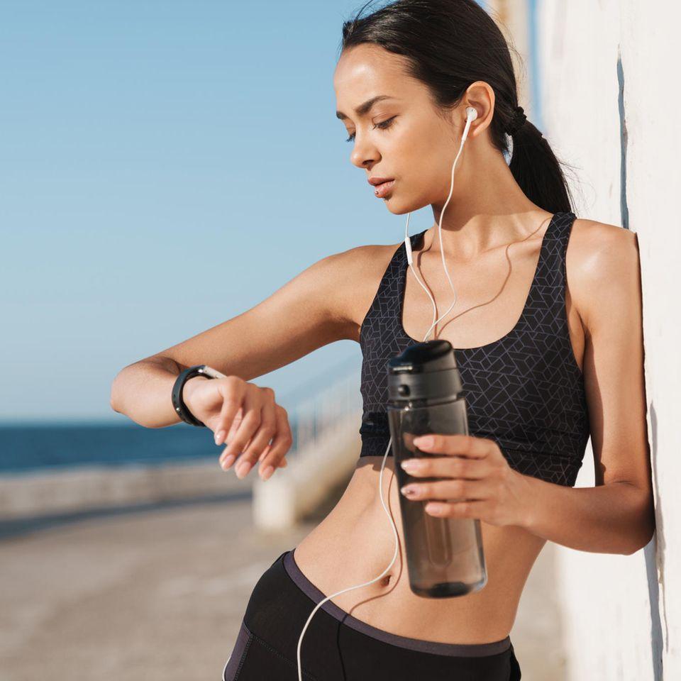 Frau beim Sport draußen, schaut aufs Fitnessarmband, Trinkflasche in der anderen Hand, Kopfhörer in den Ohren