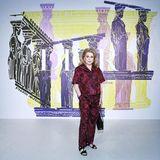 Catherine Deneuve zählt zu den ausgewählten Gästen der Dior Cruise Show in Athen. Sie trägt einen dunkelroten Zweiteiler mit Rosenprint und schwarze Sandalen.