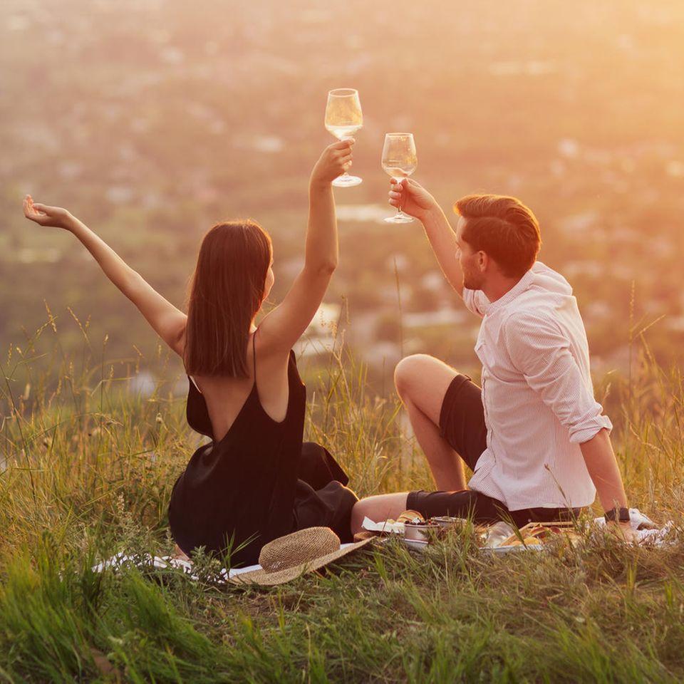 Pärchen trinkt Wein bei Sonnenuntergang