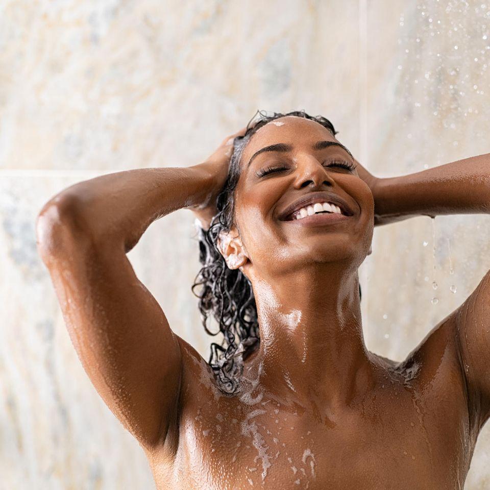 Duschöl: glückliche Frau beim Duschen mit Haarshampoo im Haar