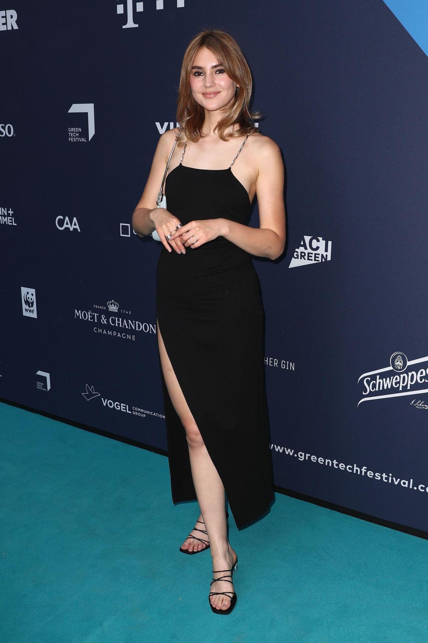 Bei den Green Awards in Berlin darf Stefanie Giesinger nicht fehlen. Sie trägt ein schwarzes Kleid mit hohem Beinschlitz und extraschmalen Kettenträgern.