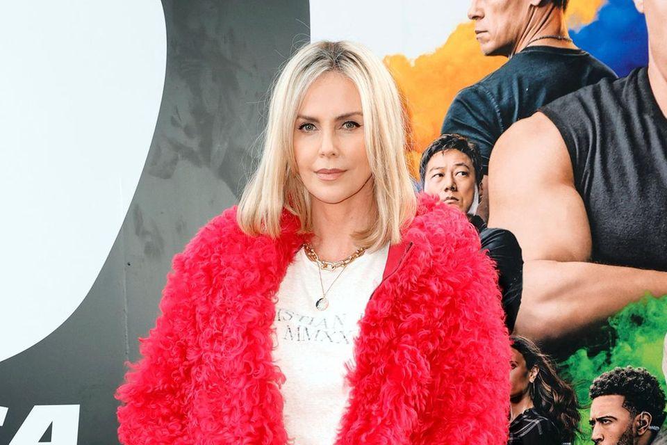 """Charlize Theron gehört eigentlich zu den absoluten Fashion-Profis auf dem Red Carpet. Bei der Premiere von """"F)"""" in Hollywood hat sie sich jedoch anscheinendvon Elmo aus der Sesamstraße inspirieren lassen. Die rote Kuschel-Jacke sieht in Kombination mit Mini-Lederrock und T-Shirt doch eher unpassend aus."""