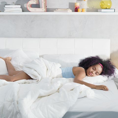 Schlafen bei Hitze: Eine Frau liegt im Bett und schläft