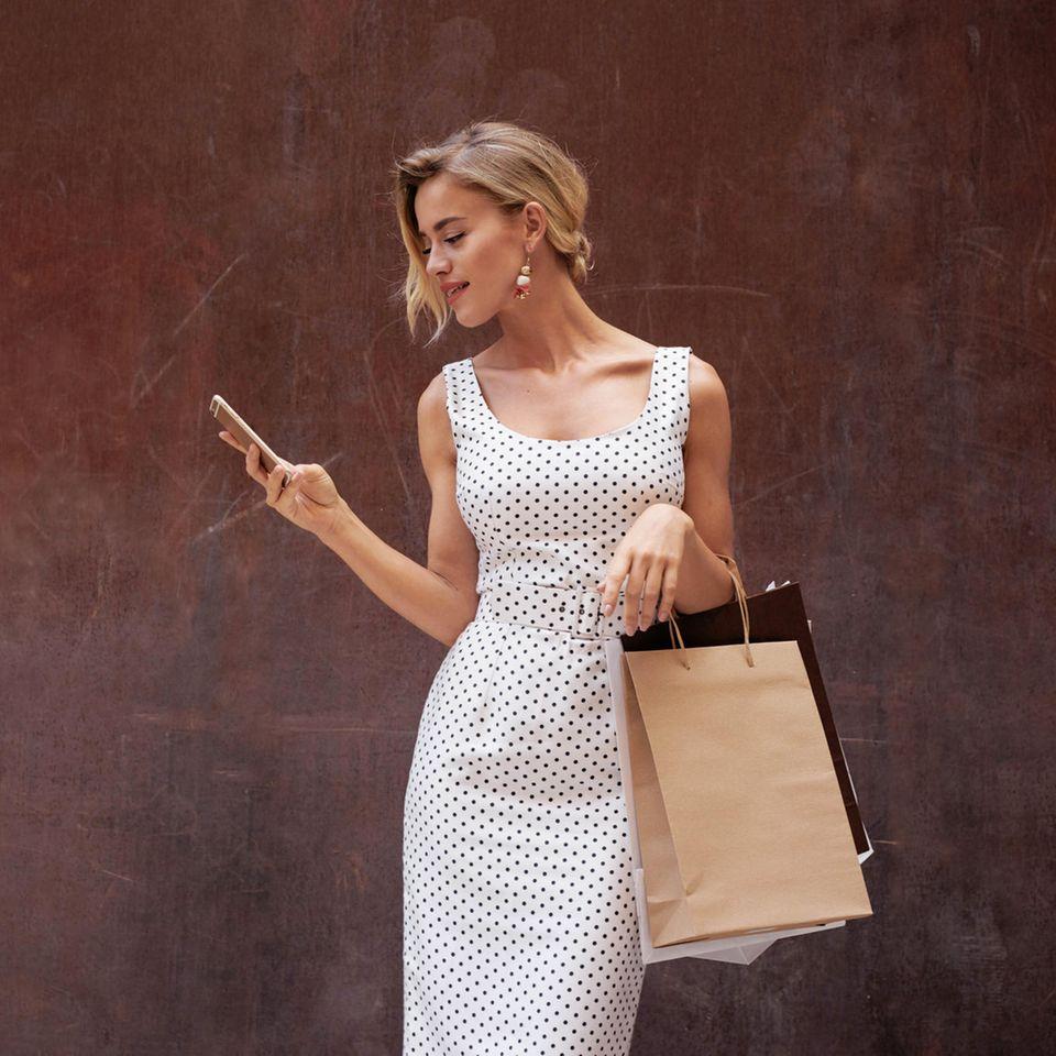 Junge Frau am Shoppen, mit Einkaufstüten in der Hand, schick angezogen
