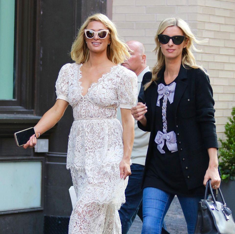 Sie könnten kaum unterschiedlicher gestylt sein:Paris und Nicky Hilton sind gemeinsam in New York unterwegs. Während Paris auf einen ultrafemininen Look aus weißem Spitzenkleid und heller Sonnenbrille setzt, trägt Nicky Blazer zur Skinny-Jeans, die Accessoires sind schwarz. Was sie aber vereint: Die Liebe zu Luxuslabels wie Valentino, Chanel und Hermès.