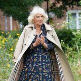 Bei der Eröffnung einer Bücherei an einer Grundschule in Cornwall macht Herzogin Camilla, wie immer, eine gute Figur. Besonders harmonisch: Die Farben des gemusterten Kleides wiederholen sich im Futter des Burberry-Trenchcoats, einem echten Lieblingsteil von Modeprofis.