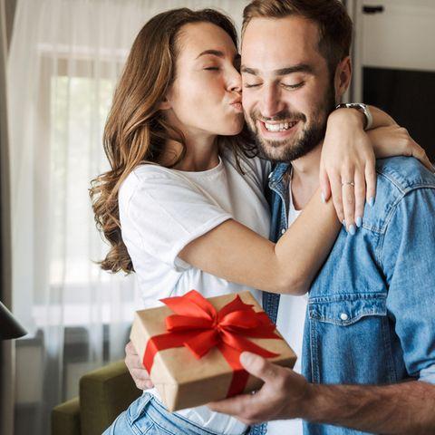 Geschenke zum Hochzeitstag: Die besten Ideen, Ein junges Paar beschenkt sich und strahlt dabei