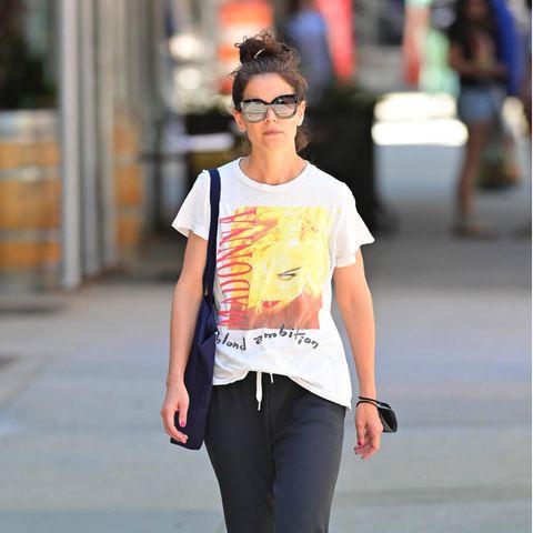 """Bei einem Spaziergang in den Straßen New Yorks zeigt sich Katie Holmes in einem ganz besonderslässigenOutfit: Sie trägt ein Fanshirt mit Popikone Madonna; darauf der Schriftzug """"Blondambition"""". Das Fanshirt scheint demnach von der gleichnamigen Tour von 1990 zu sein."""