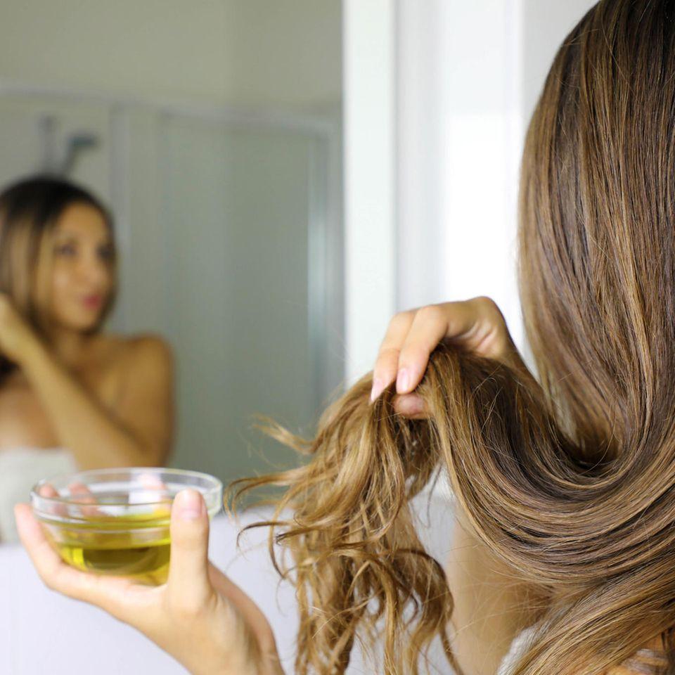 Rizinusöl, Frau vor einem Spiegel mit Haaren und Rizinusöl in der Hand