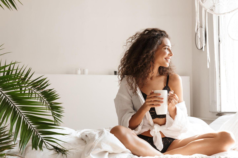 schöne Frau sitzt auf dem Bett und trinkt Tee