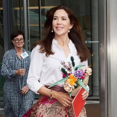 """PrinzessinMary besucht die Eröffnungsveranstaltung """"Creative Summit"""" in Kopenhagen und setzt dafür auf eine klassische weiße Bluse und einenbestickten Midirock von Valentino, die in Kombination einen romantischen Business-Look ergeben. Die rosafarbenen Rauleder-Pumps von Jimmy Choo sind eine tolle Ergänzung dazu."""