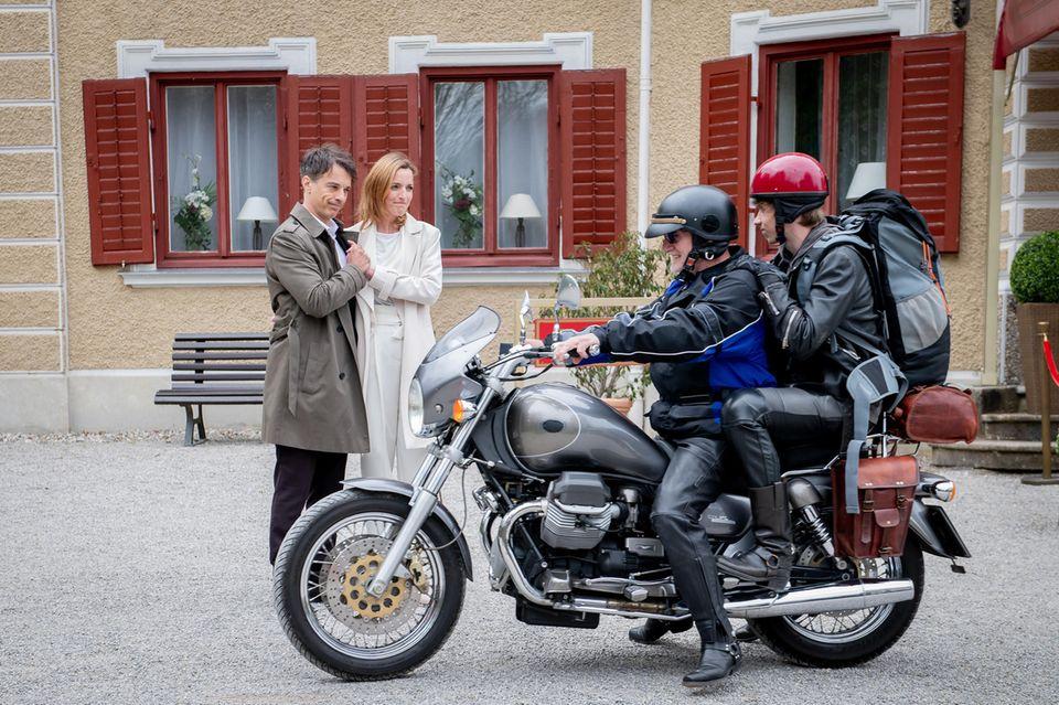 Benni (Florian Burgkart, r.) verabschiedet sich von Lia (Deborah Müller, 2.v.l.) und Robert (Lorenzo Patané, l.) und bricht mit Alfons (Sepp Schauer, 2.v.r.) in Richtung Flughafen auf.