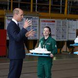 Prinz William kommt interessiert mit jungen Mitarbeiter:innen derBAE Systems-Werft ins Gespräch. Diese präsentieren dem britischen Royal stolz ihre Modelle für zukünftiggeplante Schiffe.