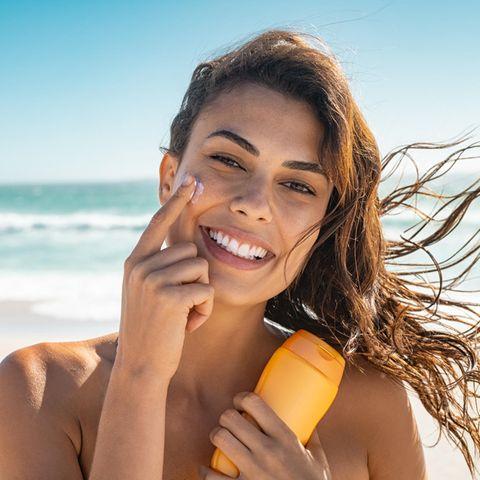 Schöne Frau am Strand mit Sonnencreme