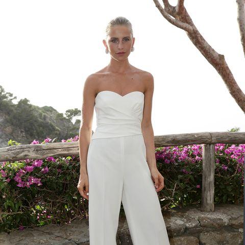 Influencerin und Unternehmerin Caro Daur verzaubert in einem Jumpsuit mit Herz-Ausschnitt und ausgestelltem Bein in der Farbe Weiß. Die Haare trägt sie zu einem streng gebundenen Dutt, auffällige Ohrringe perfektionieren ihren Look.