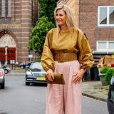 Königin Maxima in einer gelben Bluse und rosa Hose
