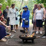 """Als weiteres Highlight im schottischen Wald, halten Prinzessin Anne und die Queen bei gegrillten Marshmallows und Lagerfeuer einen kleinen Plausch mit Gästen des""""Children's Wood Project""""."""