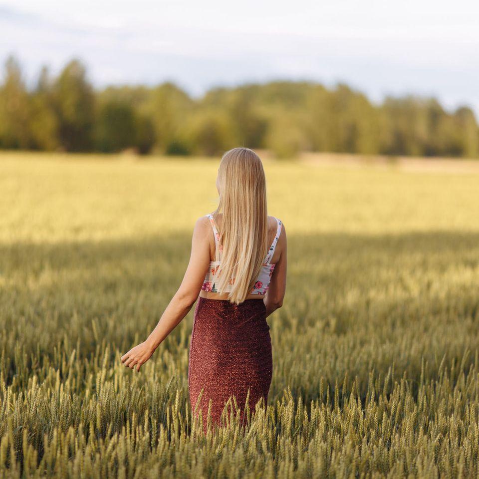 Zeckenbiss erkennen: Junge Frau läuft durch ein Getreidefeld