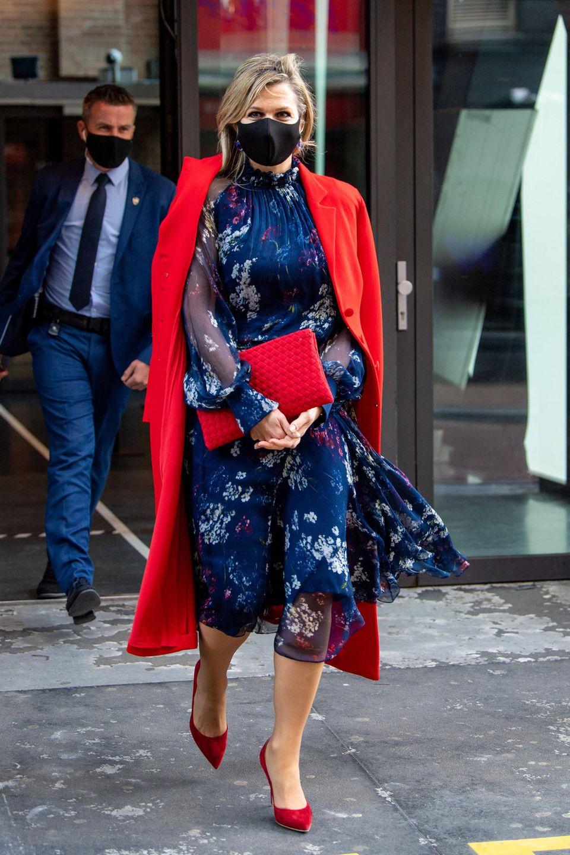 Was für eins schöner Look! Königin Máxima begeistert mal wieder mit einem floralen Sommerkleid. Dazu trägt sie knallige Pumps und eine farblich abgestimmte Clutch. Besonders auffällig ist der Mantel, der trotz seines winterlichen Schnittes in der Knallfarbe Rot sommerlich und frisch aussieht.