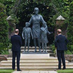 Prinz William und Prinz Harry betrachten dasimposante Denkmal, das sie zu Ehren ihrerverstorbenen Mutteranfertigen haben lassen. Prinzessin Diana wird überraschenderweise nicht alleine abgebildet, sondern zusammen mit zwei Kindern, über die sie schützend ihre Hände hält - ein starkes Symbol für ihre Gutherzigkeit und ihr soziales Engagement.