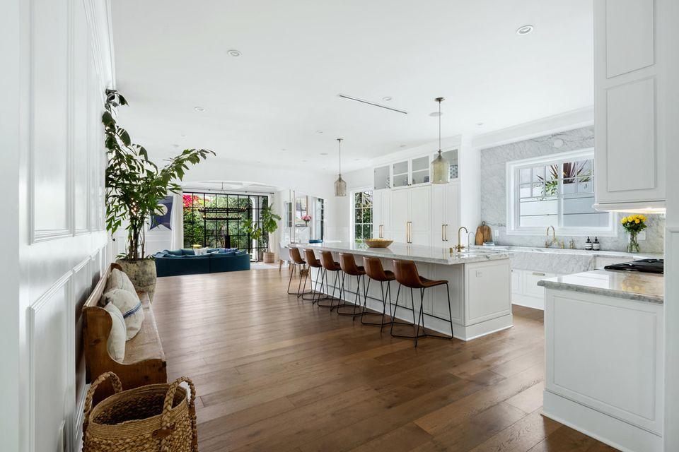 Die helle Marmor-Küche mit sehr langer Kochinsel hat Platz für jede Menge Besucher.