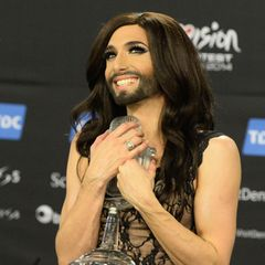 """Mit dem Song """"Rise like a Phoenix"""" gewinnt Conchita Wurst den """"Eurovision Song Contest"""" im Jahr 2014 und setzt ein Zeichen für mehr Vielfalt und Diversität in der Musikbranche.Im schicken Dress und mit gepflegtem Bart steht Conchita damals auf der Bühne in Kopenhagen, begeistert die Fans und die LGBTQIA*-Community. Hinter dem Bühnencharakter Conchita Wurst steckt übrigens der österreichische Sänger Tom Neuwirth, der die """"Diva mit Bart"""" – wie er sie nennt – selbst erschaffen hat."""