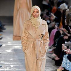 """Als Halima Aden im Februar 2017 für Max Mara über den Catwalk läuft, ist sie in der Modelbranche schon längst ein Star.Die Amerikanerin mit somalischen Wurzeln trägt Hijab und repräsentierteinen neuen Sinn für Diversitätin der Modewelt. In 2019 ist Halima Aden die erste Hijab tragende Frau auf dem Cover der beliebten Ausgabe der """"Sports Illustrated Swimsuit"""", die darauf außerdem in maßgeschneiderten Burkinis zu sehen ist. Doch im November 2020 kehrt sie dem ModelmetierdenRücken – ganz zur Überraschung ihrer vielen F ans. Die Branche habe sie gezwungen, gegen ihren Glauben zu handeln, so Halima Aden."""