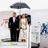 Berlin zeigt sich bei derAnkunft von König Willem-Alexanderund Königin Máxima nicht von seiner besten Seite: Der Himmel ist grau und ein Regenschirm muss das niederländische Königspaar vor Nässe schützen. Dafür ist auf Máximas modisches Gespür Verlass.Sieträgt ein weißes Kleid mit auffälligemMuster, das sich auch aufihrem Haarreifen wiederfindet. Darüber wählt die Mutter von drei Töchtern einen grünen Cardigan.
