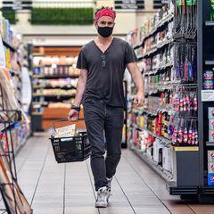 """Trotz seines unauffälligen Outfits und Mundschutz bleibt Colin Farrell auch im Supermarkt nicht unerkannt. Der Schauspieler deckt sich für das nächste Frühstück ein und so landet die Packung """"Cheerios breakfast cereals"""" ganz oben in seinem Einkaufskorb."""