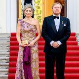 """Königin Máxima und König Willem-Alexander haben sich zum Staatsbesuch in Berlin in Schale geworfen. Nicht nur das fliederfarbene Abendkleid von Jan Taminiau mit 3D-Blumen-Applikationen und einem One-Shoulder-Schnittist ein Meisterwerk. Auch die Juwelen, die Máxima für den Abend wählt, ziehen alle Blicke auf sich. Dazu setzt die Mutter von drei Töchtern auf eine Clutch vonBegum Khanin Gold mit einem aufgestickten """"Evil Eye"""". Doch es wartet noch ein weiteres Highlight ..."""
