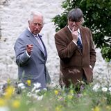"""6. Juli 2021  Im Rahmen der jährlichen """"Wales Week"""" lädt Prinz Charles den Schriftsteller und HofdichterSimon Armitage zu einem Rundgang über sein walisisches Anwesen Llandovery ein. Stolz präsentiert der Royal seinen üppigen grünen Garten."""