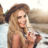 Strandfrisuren: Frau mit offenen Haaren und Hut