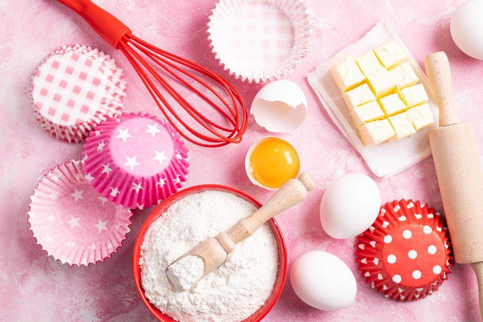 Backzubehör: Schneebesen, Nudelholz, Muffinformen, Eier, Mehl, Schüssel