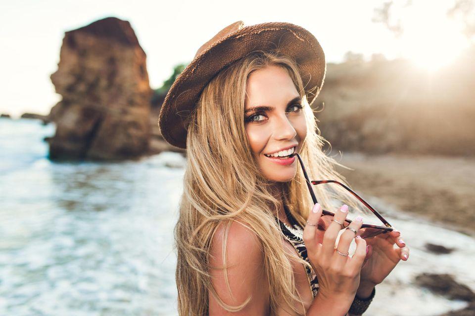 Strandfrisuren: Frau am Strand mit Hut