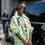 """So posiert Jodie Turner-Smith bereits einige Wochen vor dem offiziellen Launch mit der """"Diana Tote Bag"""". Sie kombiniert die Tasche mit einem Zweiteiler aus Jeans in der Farbe Grün und einer lässigen Sonnenbrille im Hippie-Look."""