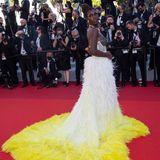 """Zur """"Stillwater""""-Premiere in Cannes präsentiert Jodie Turner-Smith bereits einen zweiten Hingucker-Look im Rahmen der Filmfestspiele: Die Schauspielerin setzt auf eine Robe mit Corsagen-Oberteil, die an einen mit Federn besetzen Rock mit Schleppe knüpft."""