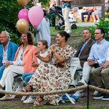 An diesem wunderschönen Sommerabend lauscht die königliche Familie in fröhlicher Runde den Klängen desKonzertes. Die bunten Ballons fürGeburtstagskind Victoria werden dabei vonPrinzessin Estelle, die ihrer Mama nicht von der Seite weicht, in Obhut genommen.