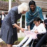Das junge Mädchen freut sich über so viel Aufmerksamkeit der Herzogin und zeigt Camilla stolz ihr schickes Kleid.