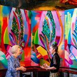 """Prinzessin Beatrix is ebenfalls bei der Preisverleihung anwesend. Beim Rundgang durch dieSonderausstellung """"Grenzforscher, Königlicher Preis für freie Malerei 150 Jahre"""" kommt Beatrix mit der Künstlerin des farbenfrohen Gemäldes ins Gespräch. Die niederländische Royal ist begeistert, mehr über die Entstehungsgeschichte der präsentierten Kunst zu erfahren."""